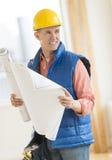 Arquiteto Looking Away While que guarda o modelo na construção S fotografia de stock royalty free