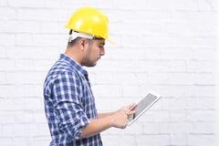 Arquiteto masculino farpado novo que trabalha na tabuleta que pensa sobre bu fotografia de stock