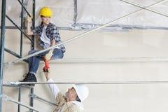 Arquiteto masculino que dá a broca ao trabalhador fêmea no andaime no canteiro de obras Fotografia de Stock Royalty Free