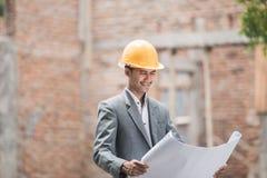 Arquiteto masculino que olha seu plano da casa fotos de stock