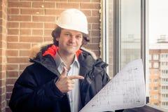 Arquiteto no capacete de segurança, guardando o olhar de sorriso dos modelos na câmera e nos pontos seu dedo ao desenho Foco maci Imagem de Stock