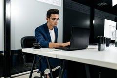 Arquiteto novo de cabelo escuro vestido em trabalhos de um casaco azul no portátil no escritório imagens de stock