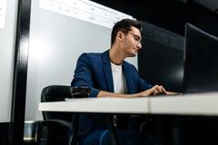 Arquiteto novo de cabelo escuro vestido em trabalhos de um casaco azul no portátil no escritório fotos de stock royalty free
