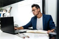 Arquiteto novo de cabelo escuro vestido em trabalhos de um casaco azul no portátil no escritório fotos de stock