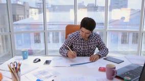 Arquiteto novo, homem de negócios no escritório limpo brilhante moderno que trabalha com modelo e planos video estoque