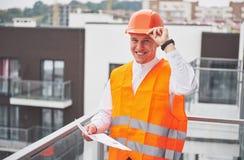 Arquiteto novo que veste um capacete protetor que está nas montanhas que constroem o fundo exterior Foto de Stock