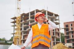 Arquiteto novo que veste um capacete protetor que está nas montanhas que constroem o fundo exterior Imagem de Stock Royalty Free