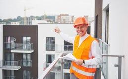 Arquiteto novo que veste um capacete protetor que está nas montanhas que constroem o fundo exterior Imagens de Stock