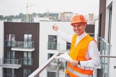Arquiteto novo que veste um capacete protetor que está nas montanhas que constroem o fundo exterior Imagem de Stock