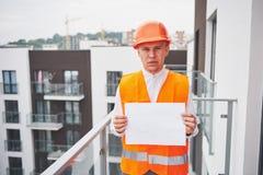 Arquiteto novo que veste um capacete protetor que está nas montanhas que constroem o fundo exterior Fotografia de Stock