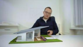 Arquiteto que ajusta o telhado e a associação em um housemodelono escritório vídeos de arquivo