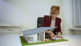 Arquiteto que ajusta o telhado e a associação em um housemodelono escritório video estoque
