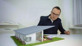 Arquiteto que ajusta a piscina em um housemodelono escritório filme