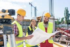 Arquiteto que compartilha de ideias sobre o plano do projeto imobiliário no canteiro de obras fotos de stock