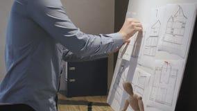 Arquiteto que põe um esboço sobre um whiteboard filme
