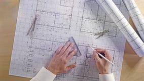 Arquiteto que toma medidas no plano arquitetónico da construção de casa do modelo com lápis, régua, compassos e o flatlay quadrad filme
