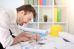 Arquiteto que trabalha em seu papel dos projetos no escritório Fotografia de Stock