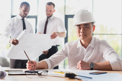 Arquiteto que trabalha no projeto novo com colegas atrás Imagem de Stock