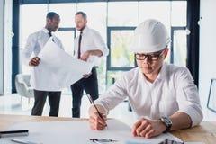 Arquiteto que trabalha no projeto novo com colegas atrás Fotos de Stock