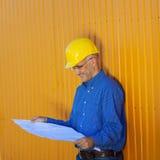 Arquiteto Wearing Hardhat While que analisa a cópia azul fotos de stock