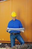 Arquiteto Wearing Hardhat While que examina a cópia azul foto de stock royalty free