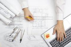 Arquiteto Working On Blueprint Local de trabalho dos arquitetos - projeto arquitetónico, modelos, régua, calculadora, portátil e Fotografia de Stock