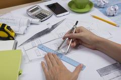 Arquiteto Working On Blueprint Local de trabalho dos arquitetos - projeto arquitetónico, modelos, régua, calculadora, portátil e Fotos de Stock Royalty Free