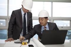 Arquitetos asiáticos que trabalham no planeamento Imagens de Stock Royalty Free
