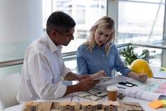Arquitetos dos Caucasians que discutem sobre o modelo na mesa no escritório fotos de stock