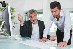 Arquitetos incomodados que olham planos no escritório fotos de stock