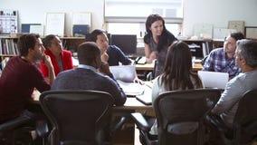 Arquitetos que sentam-se em torno da tabela que tem a reunião video estoque
