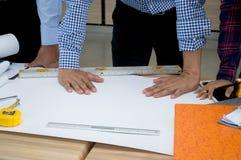 Arquitetos que trabalham com modelos, inspecionando o engin do local de trabalho fotografia de stock royalty free