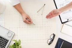 Arquitetos que trabalham no modelo, projeto dos bens imobiliários Local de trabalho do arquiteto - projeto arquitetónico, modelos Imagem de Stock
