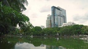 Arquitetura da cidade: arranha-céus e parque no distrito financeiro Vista dos prédios de escritórios através do lago no parqu vídeos de arquivo