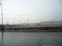 A arquitetura da cidade atrás do vidro com chuva deixa cair foto de stock