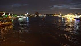 Arquitetura da cidade Banguecoque do centro na noite, e barco da longo-cauda que move-se através do rio no primeiro plano vídeos de arquivo