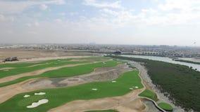A arquitetura da cidade de Ajman com golfe coloca a vista superior aérea video estoque