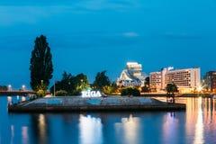 Arquitetura da cidade de Riga Letónia na iluminação de noite Vista da terraplenagem do rio do Daugava Imagens de Stock