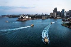 Arquitetura da cidade de Sydney com teatro da ópera e de ferryboats no oceano após o por do sol, Sydney, Austrália imagens de stock