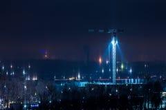 Arquitetura da cidade do inverno da noite com fenômeno atmosférico das colunas claras foto de stock