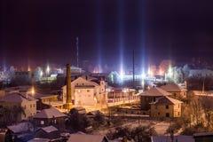 Arquitetura da cidade do inverno da noite com fenômeno atmosférico das colunas claras fotos de stock