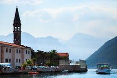 Arquitetura da cidade e barco no fundo das montanhas Vista da cidade velha de Perast na baía de Kotor, Montenegro Foto de Stock