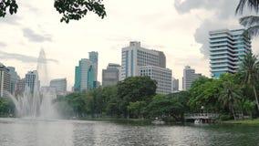 Arquitetura da cidade: fonte, palmeiras, lago e arranha-céus Construção moderna ao lado de um parque verde, conceito da cidade video estoque