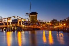 Arquitetura da cidade - opinião da noite do canal da cidade com ponte levadiça e moinho de vento, a cidade de Leiden fotos de stock