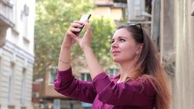 Arquitetura de fotografia de sorriso nova da mulher na rua com seu smartphone vídeos de arquivo