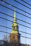 A arquitetura de Londres, distrito financeiro, reflete de uma igreja em uma construção Fotos de Stock Royalty Free