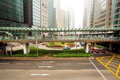 Arquitetura do vidro e do concreto em uma cidade enorme com os carros de Hong Kong Imagem de Stock