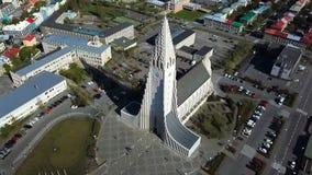 Arquitetura moderna de Islândia Reykjavik da vista geral da igreja de Hallgrimskirkja Imagens de vídeo aéreas para baixo cidade d video estoque