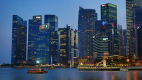 Arquitetura moderna iluminada de Singapura e barco de turista em Singapura video estoque