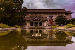 Arquitetura simétrica sob um céu azul e reflexões em uma lagoa com tons verdes imagens de stock